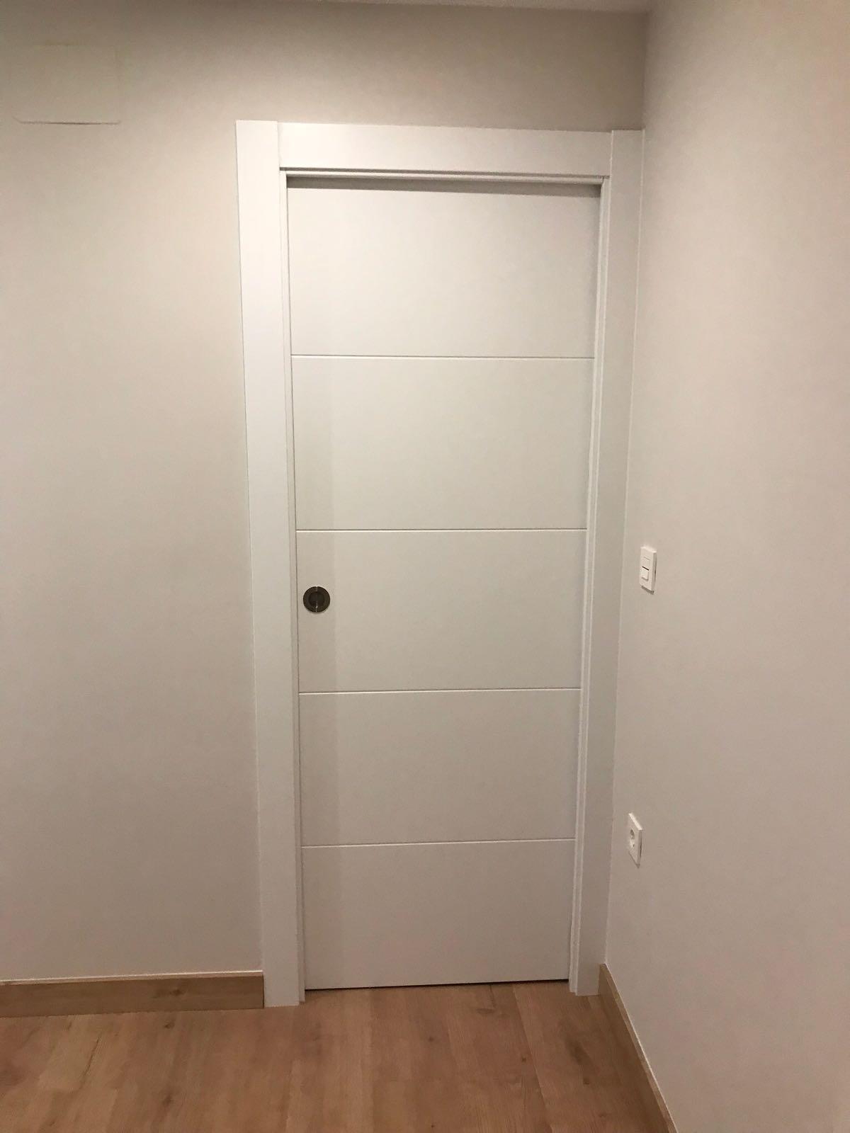 Puertas blanca puerta blindada blanca con lineas fresadas for Puerta blindada blanca