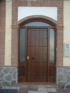 Puerta de entrada con fijo lateral y arco superior