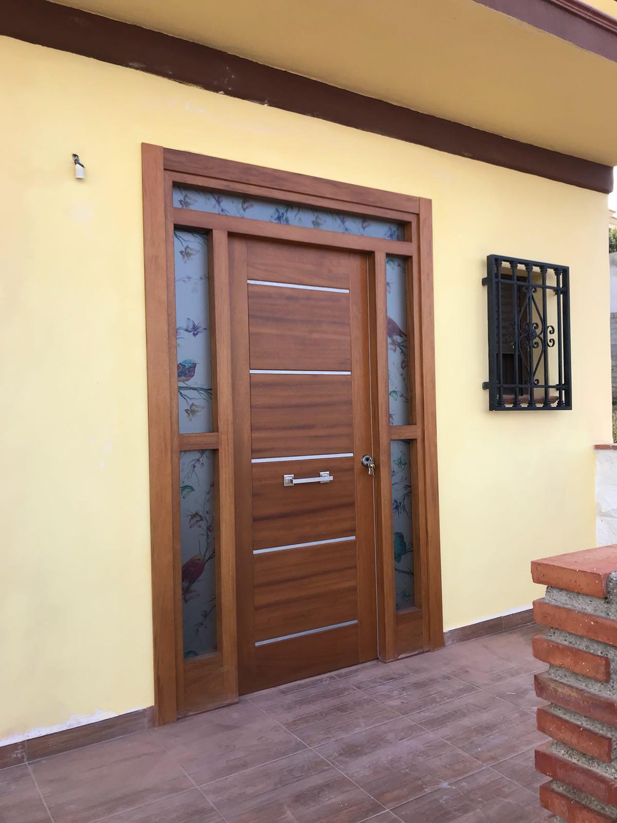 Puerta de entrada color madera con marco amplio decorado en granada carpinteria movidecor granada - Puertas de entrada con cristal ...