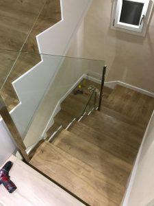 Escaleras de madera con baranda de cristal